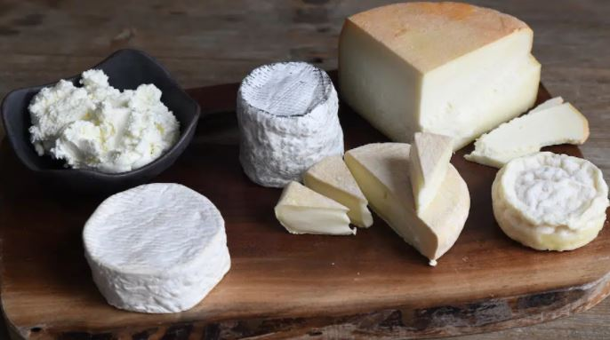 a wooden platter of artisan cheese sits ready to eat at green dirt farm