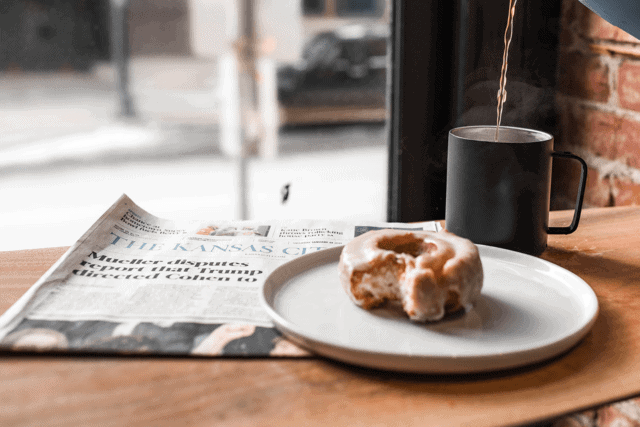 A donut sits next to a fresh cup of coffee and a copy of the Kansas City newspaper
